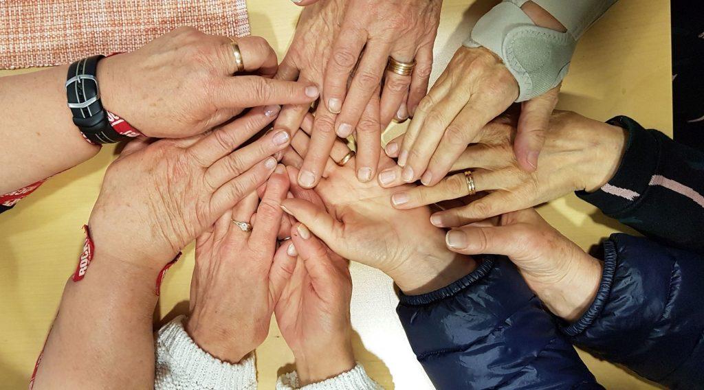 Isosiskot-ryhmän naisten käsiä. Iäkkäitä käsiä, joissa on sormuksia, kinesioteippiä ja rannetuki.