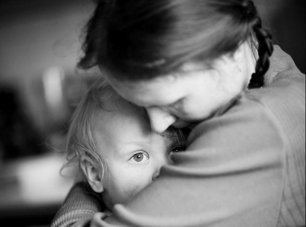 Äiti suojaa lasta sylissään, mustavalkoinen kuva.