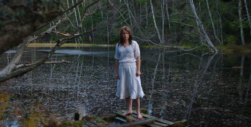 Nainen metsäisellä järvellä, seisoo rikkonaisella laiturilla valkoisissa vaatteissa.