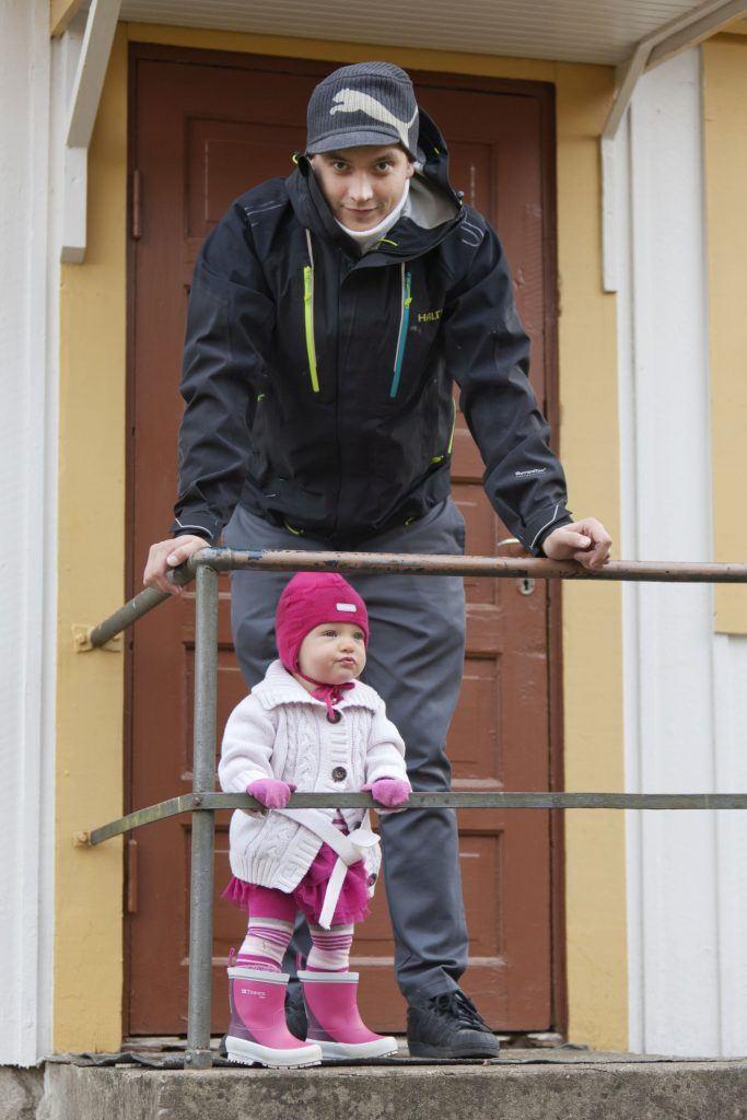 Turvallinen isä ja pieni tyttö portailla katsomassa eri suuntiin. Kuvan isä ei ole Jussi-työn asiakas.